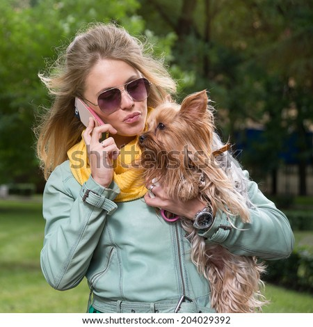 Girl talking cell phone and kissing her dog - stock photo