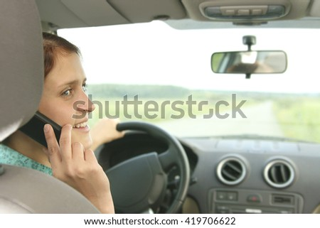 Girl talking on mobile while driving. Portrait of young woman holding in hands cell phone inside car. Copy space for inscription. Taxi Girl call customer Empty place - stock photo
