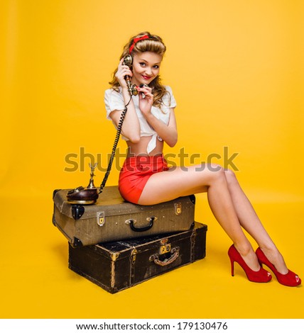 girl talking on the phone sitting on suitcases - stock photo