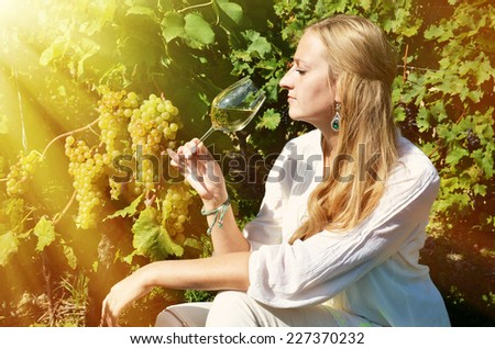 Girl tasting white wine among vineyards. Lavaux, Switzerland - stock photo