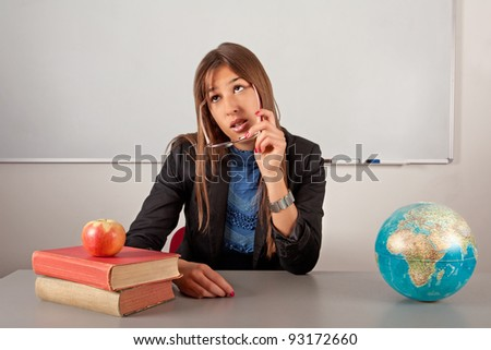 Girl teacher sitting in school and thinking