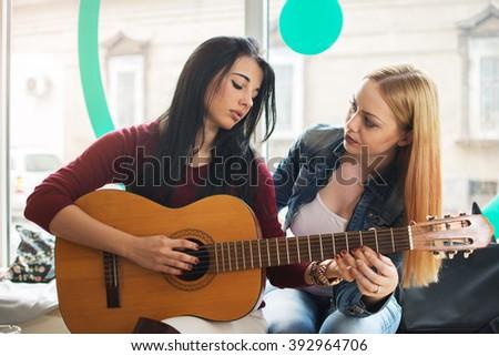 Girl teaching her friend to play guitar. - stock photo