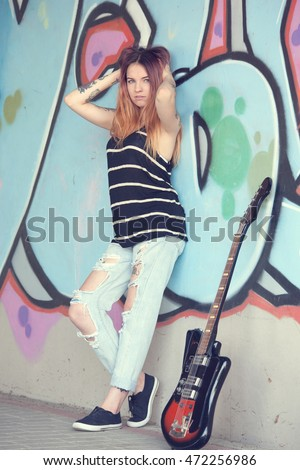 Girl teen with electric guitar stands near the wall of graffiti.