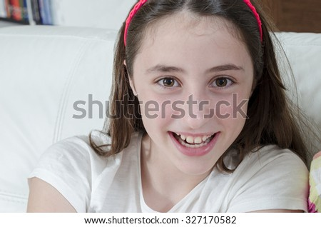 Girl teenage brunette is looking at camera with smile, close-up. - stock photo