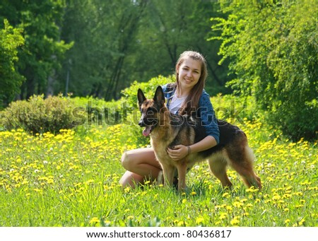 girl, teenager has a rest on a green lawn with a dog a German shepherd