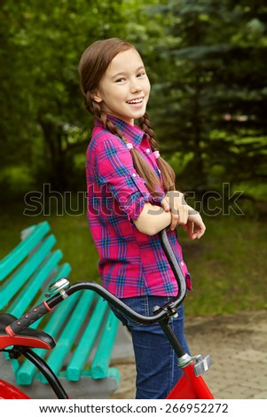 Girl teenager in a park with a bicycle . Active people. Outdoors