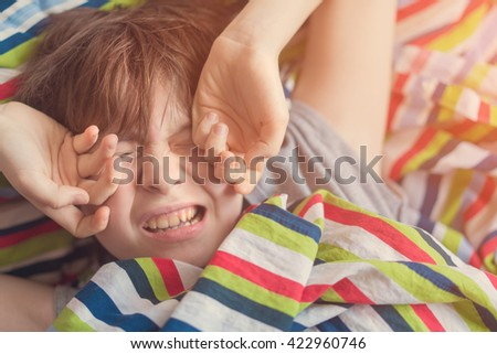 Girl teenager in gray pajamas stretching in bed under a striped colored blanket - stock photo