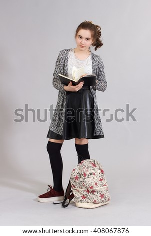 Girl teenager with books and backpacks on a gray background in full length . - stock photo