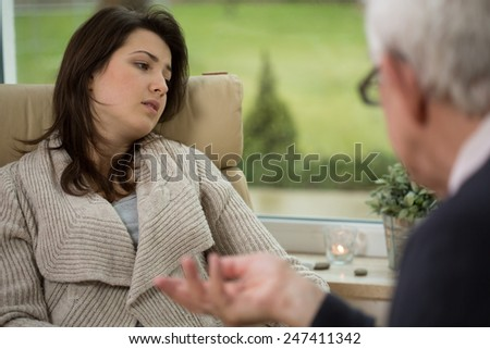 Girl telling about her troubles during psychotherapy session - stock photo