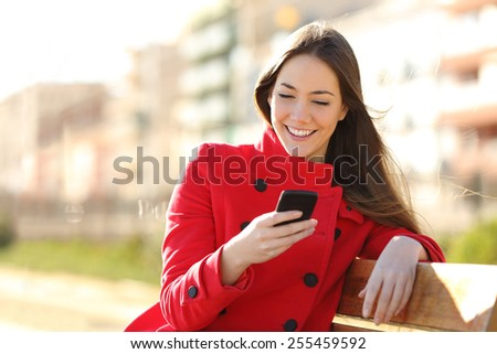 Girl texting on the smart phone sitting in a park wearing a red jacket and sitting in a bench in a park - stock photo