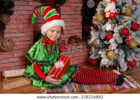 Girl - the Christmas elf with a gift near Xmas fir-tree and fireplace - stock photo
