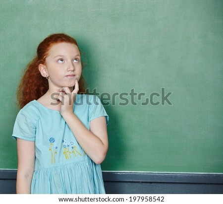 Girl thinking at chalkboard in elementary school class - stock photo