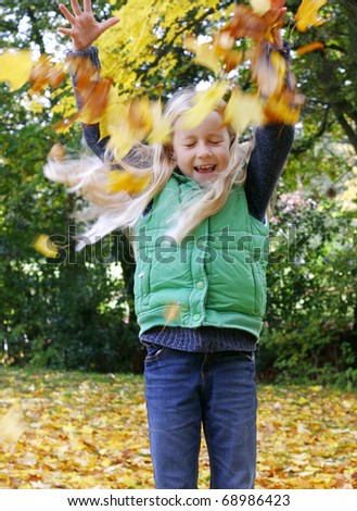 Girl throwing leaves in autumn park - stock photo