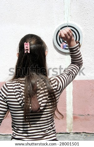 Girl  throws javelin to dartboard - stock photo