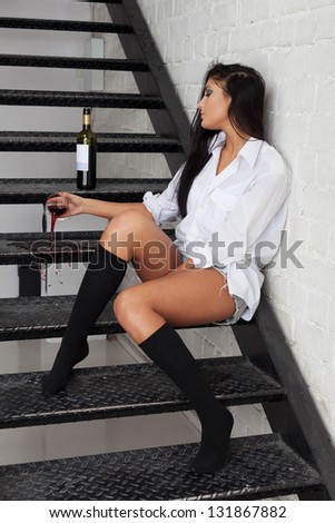 Girl tired of drinking and pouring red wine out of glass - stock photo