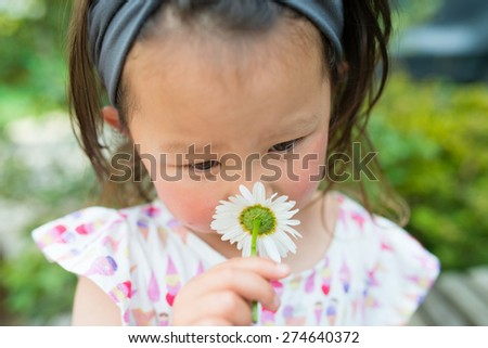 girl to smell the scent of Margaret - stock photo