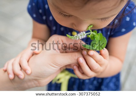 Girl to smell the scent of mint flowers - stock photo