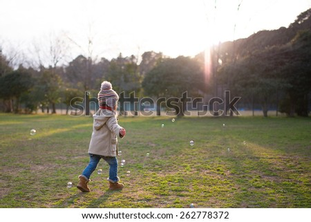 Girl to the bubble play in the park to refer the sunset - stock photo