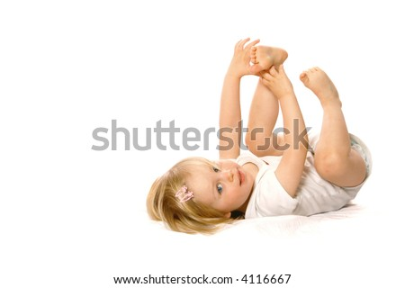 Girl toddler in white vest having fun playing with her toes.