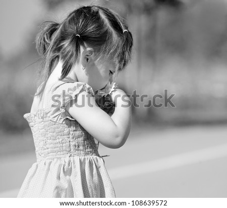 girl toddler is having fun smelling flower in the summer
