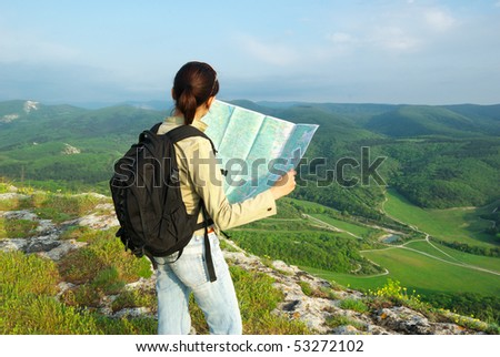 Girl tourist in mountain read the map. - stock photo