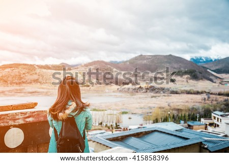girl tourist standing alone by the mountain  landscape during  summer vacation with his backpack back view - stock photo
