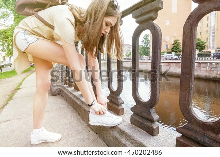 Girl tourist with black fitness bracelet adjusts laces on white sneakers. White girl with long brown hair and sunglasses on her head and a small backpack. Outdoors. Sunny effect. - stock photo