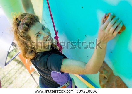 Girl train climbing on a artificial rock outdoors - stock photo