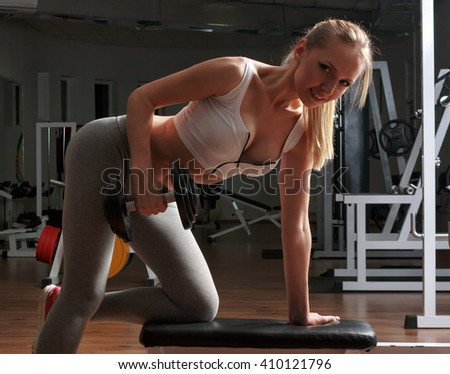 Girl trains with dumbbells in the gym