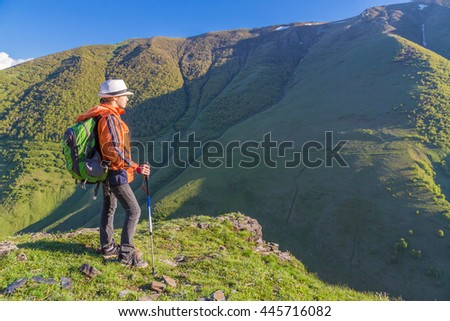 Girl traveling on mountains hills with backpack - stock photo