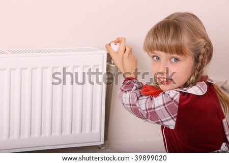 Girl try open thermostat. Energy crisis. - stock photo