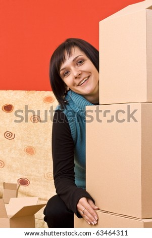 Girl trying to lift a stack of heavy cardboard boxes. - stock photo