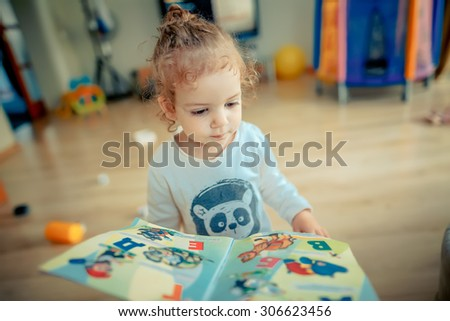 girl trying to read a children's book