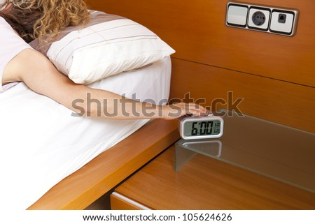 Girl turning off the alarm clock at 6 o'clock in the morning