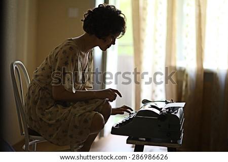 girl typing on a typewriter - stock photo