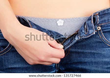 Girl unbuttoned jeans, close-up hands