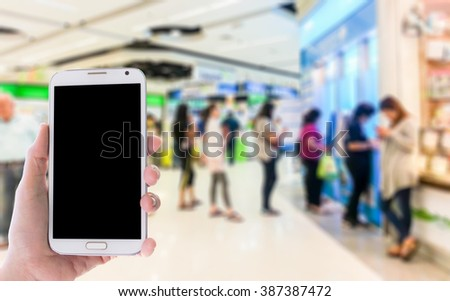 Girl use mobile phone, blur image of people stand at ATM machine as background. - stock photo