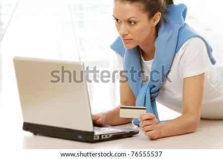 Girl using a card to shop safely online isolated on white background