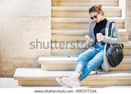Girl using a cell phone outdoors. - stock photo