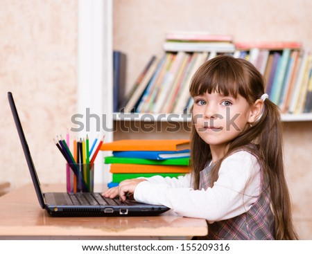 Girl using a laptop computer at school - stock photo