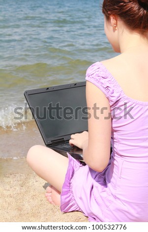 girl using a laptop on the beach - stock photo