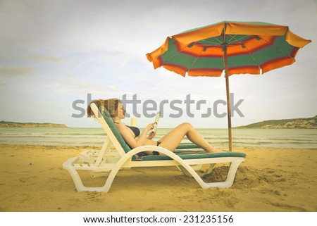 Girl using a tablet at the beach  - stock photo
