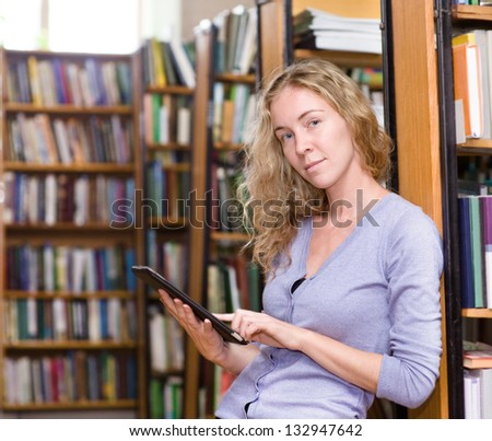 girl using a tablet computer in a library