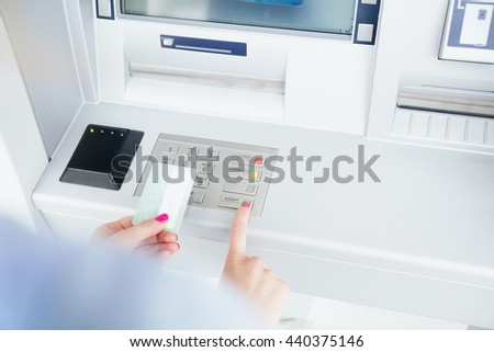 Girl using ATM machine. - stock photo