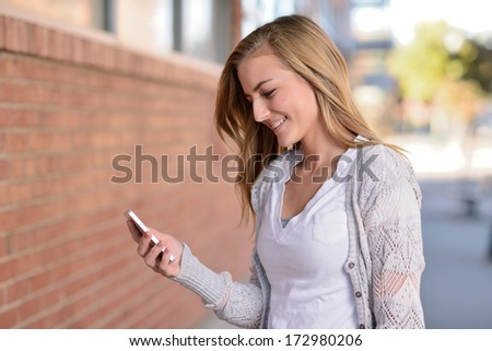 Girl using smartphone. Teen girl holding a cell phone and smiling outside on a city street. - stock photo