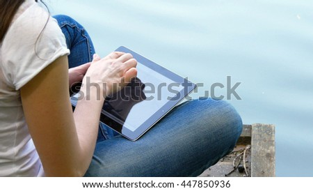 Girl using tablet pc and relaxes by the lake sitting on the edge of a wooden jetty near the water surface - stock photo