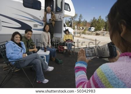 Girl videotaping family outside of RV - stock photo