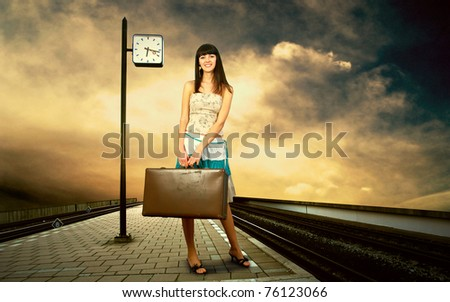 Girl waiting train on the platform of railway station - stock photo