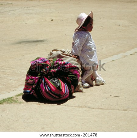 Girl waiting with baggage for transport, Bolivia