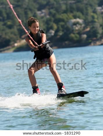 Girl wakeboarding on the lake - stock photo